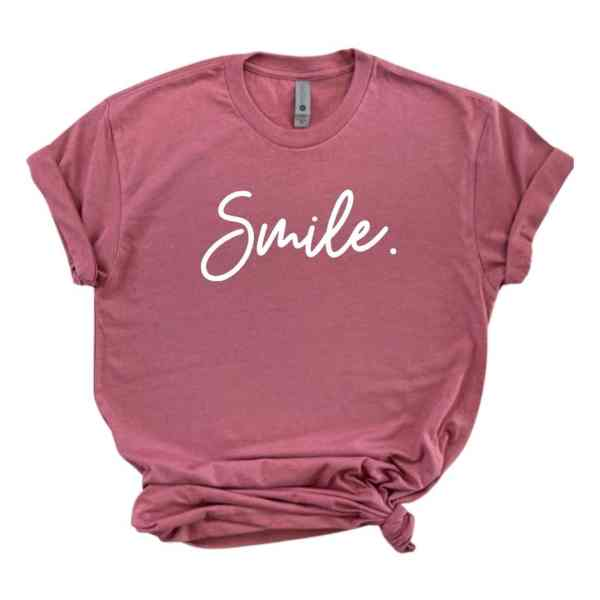 Rose mauve shirt with smile written in white cursive font