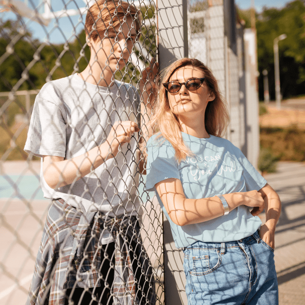 Female wearing light blue shirt with you can and you will written in white cursive lettering in front of a gate with a male behind it