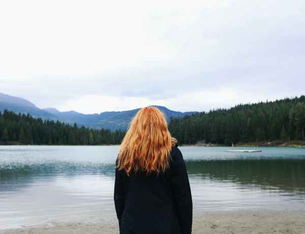 anonymous female on shore enjoying view of lake near forest