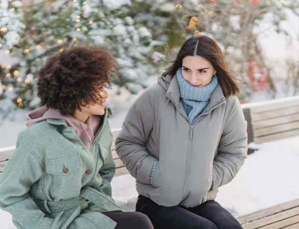diverse female friend talking on bench in winter park