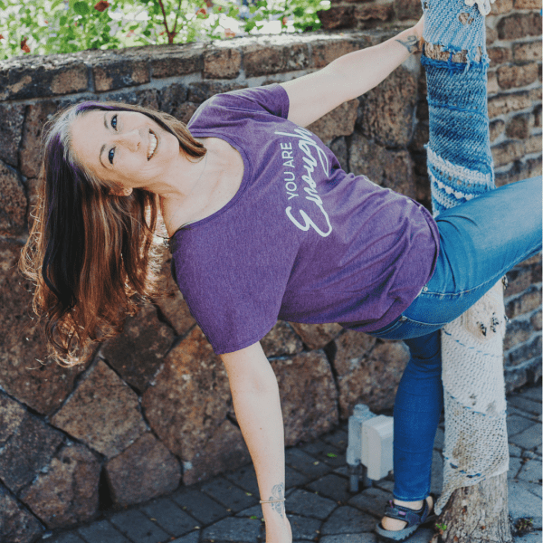 A woman with her leg around a tree wearing a You Are Enough Scoop Neck Shirt in Vintage Purple