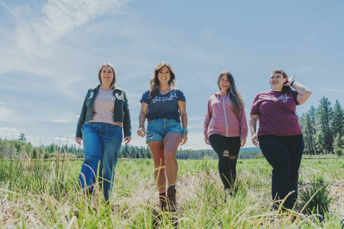 Four average women walking in a field with uplifting shirts on