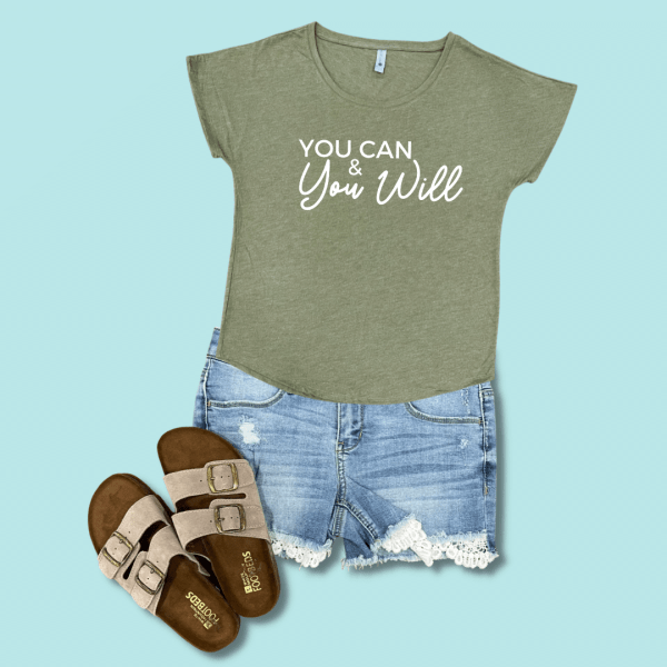Blue background with green shirt, jean shorts, and sandals