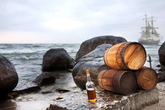 3 Barrels of rum stacked in front of a stormy sea with a pirate ship on the horizon