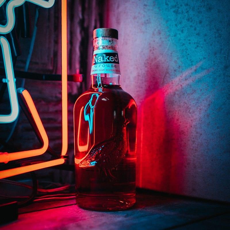 Naked Grouse Whisky Bottle in front of Neon Lights