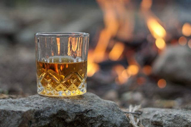 Whisky in a glass in front of a campfire