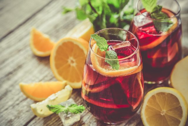 A glass of sangria surrounded by ingredients