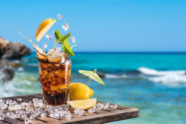 A rum cocktail sitting in front of the sea