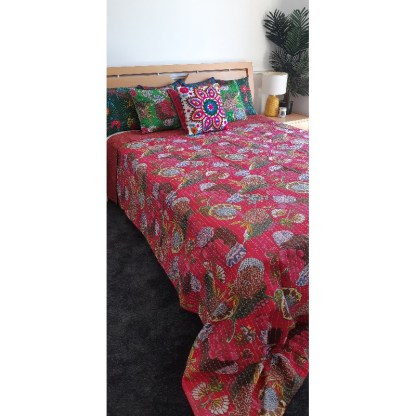 Bright pink bedding and coloured cushions on bed