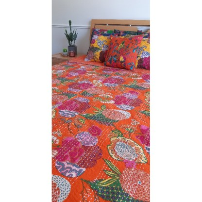 orange patterned bedspread and bright cushions