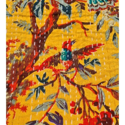 yellow kantha fabric with bird in trees printed on it