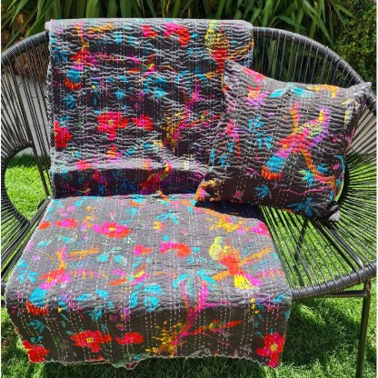 Black tropical print throw blanket and scatter cushion on outdoor chair