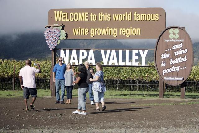 Napa County's wine-centric economy has some wondering if a little more economic diversity is needed. Here, tourists in 2018 take turns photographing each other in front of the welcome sign along Highway 29 near Oakville. Register photo