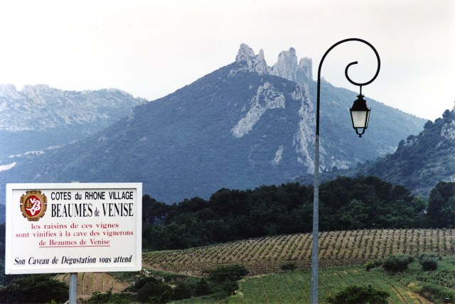 The Dentelles in the background to a sign touting the Côte du Rhône-Villages wines of Beaumes de Venise. Phillip Capper - originally posted to Flickr as Dentelles de Montmarail from Beaumes de Venise