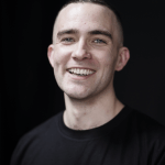 A headshot of Guy Lochhead, he has close cropped dark brown hair and is smiling and looking at the camera
