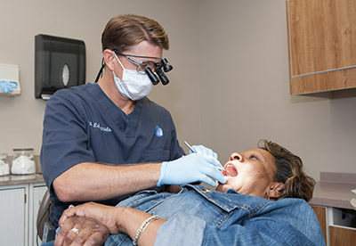 A male dentist checking on the woman's teeth - Mississauga Dentist - Bristol Dental