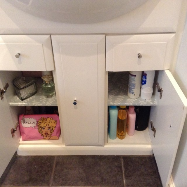 lining a bathroom cabinet with wallpaper