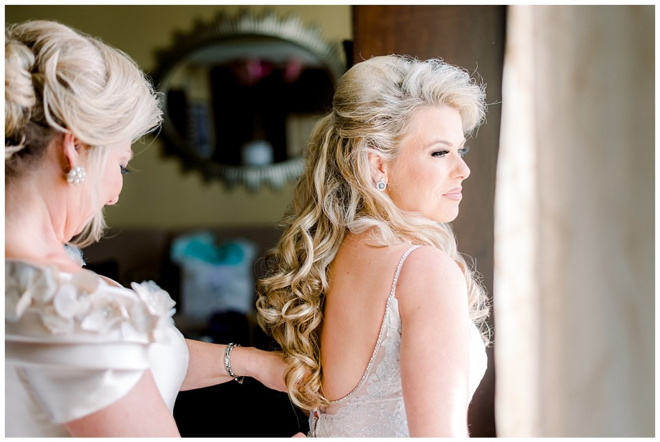 bride being zipped up by her mom on wedding day