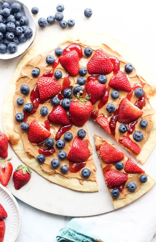 A picture of peanut butter spread on a tortilla with fresh blueberries and strawberries.