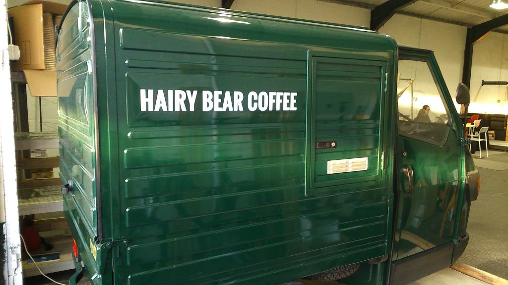 The Hairy Bear Coffee van, Audrey. A very small green van with Hairy Bear Coffee written on the side.