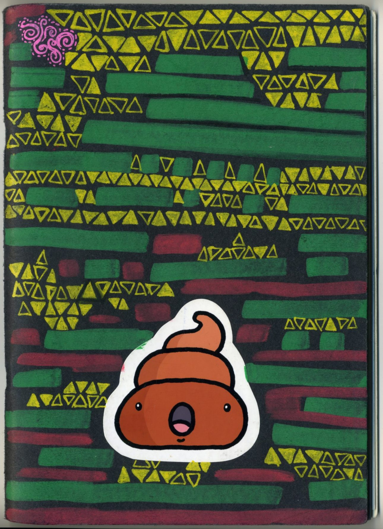The front cover of my 2015 - 2016 sketchbook, a black cover with green, yellow and pink mark making patterns and a cute cartoon surprise poo sticker.
