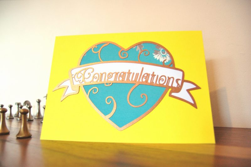 Layered paper cut Art Nouveau Congratulations Card in yellow with a blue patterned heart.