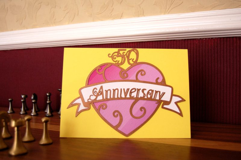 Layered paper cut Art Nouveau Congratulations Card in yellow with a pink patterned heart. This example was a custom commision for a 50th Anniversary so reads Anniversary instead of Congratulations.