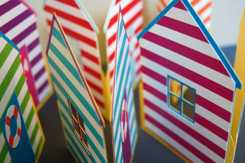 A close up of Beach Hut card, purple with blue stipes and blue with pink stripes.