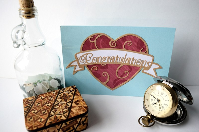 Layered paper cut Art Nouveau Congratulations Card in pastel blue with a red patterned heart.