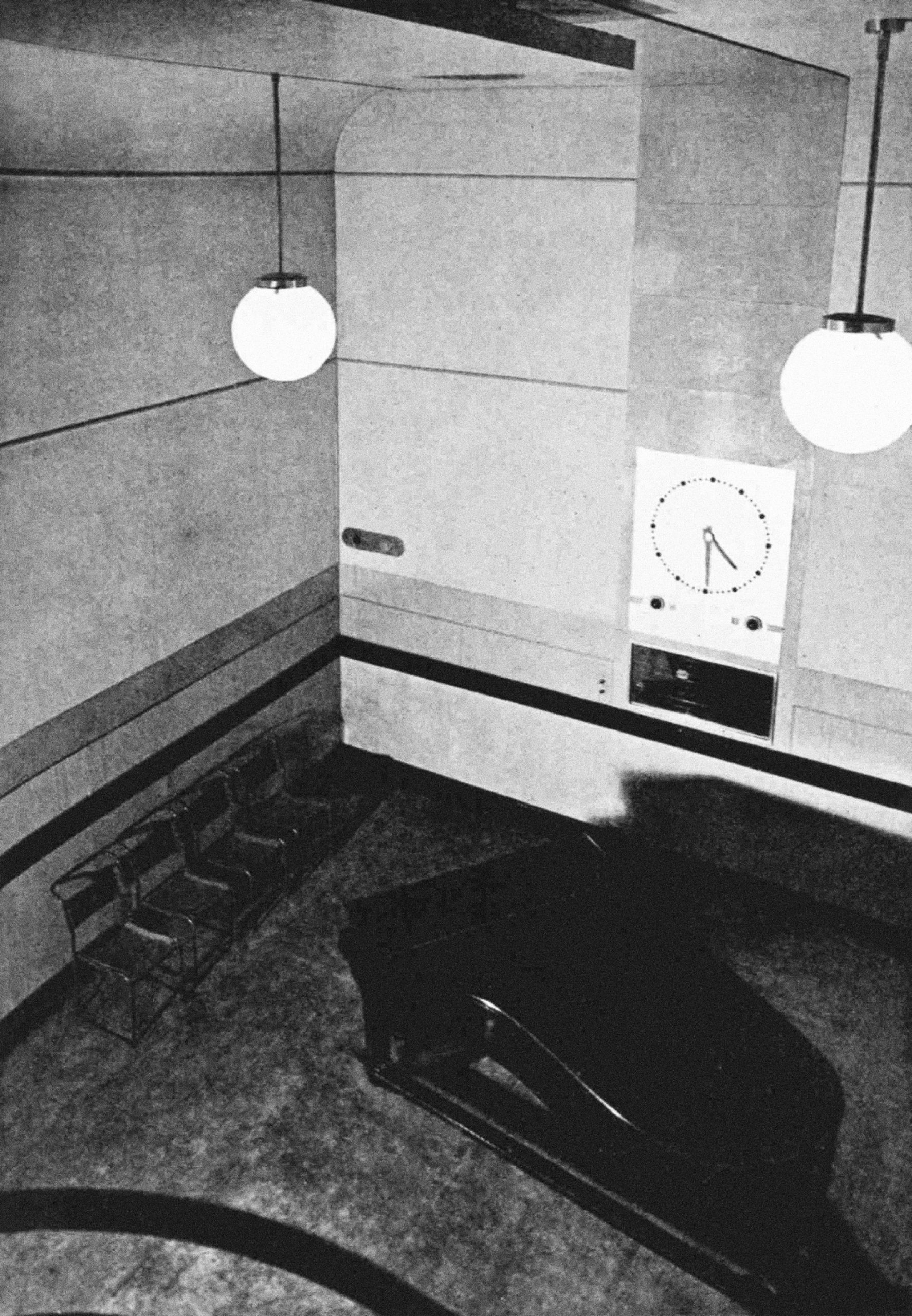 Looking down into studio with a piano and a very large illuminated clock