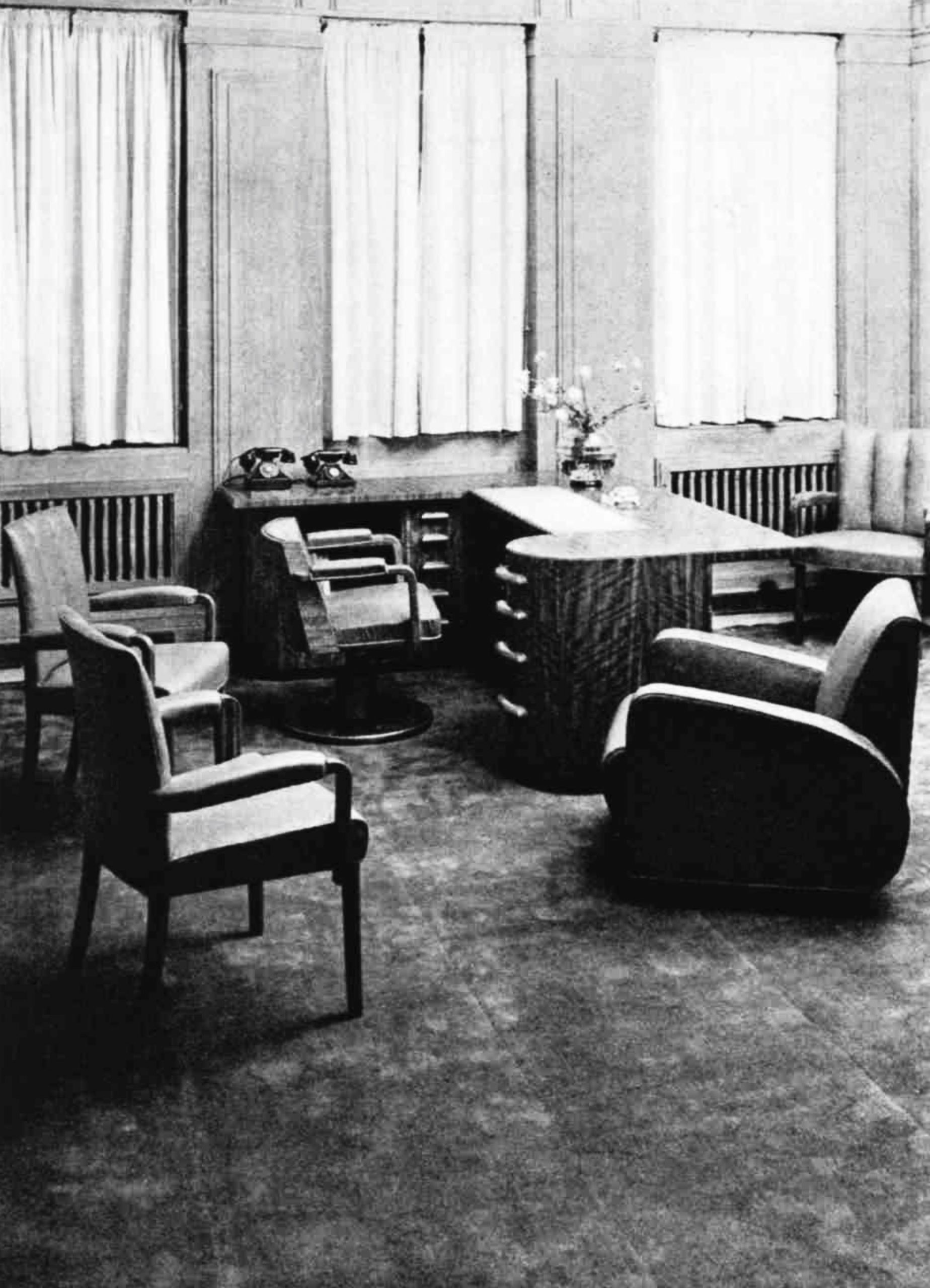 A office with a fitted desk with two telephones surrounded by 5 chairs in 3 different styles