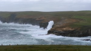 Sea spray hits the cliffs by the Broch of Borwick