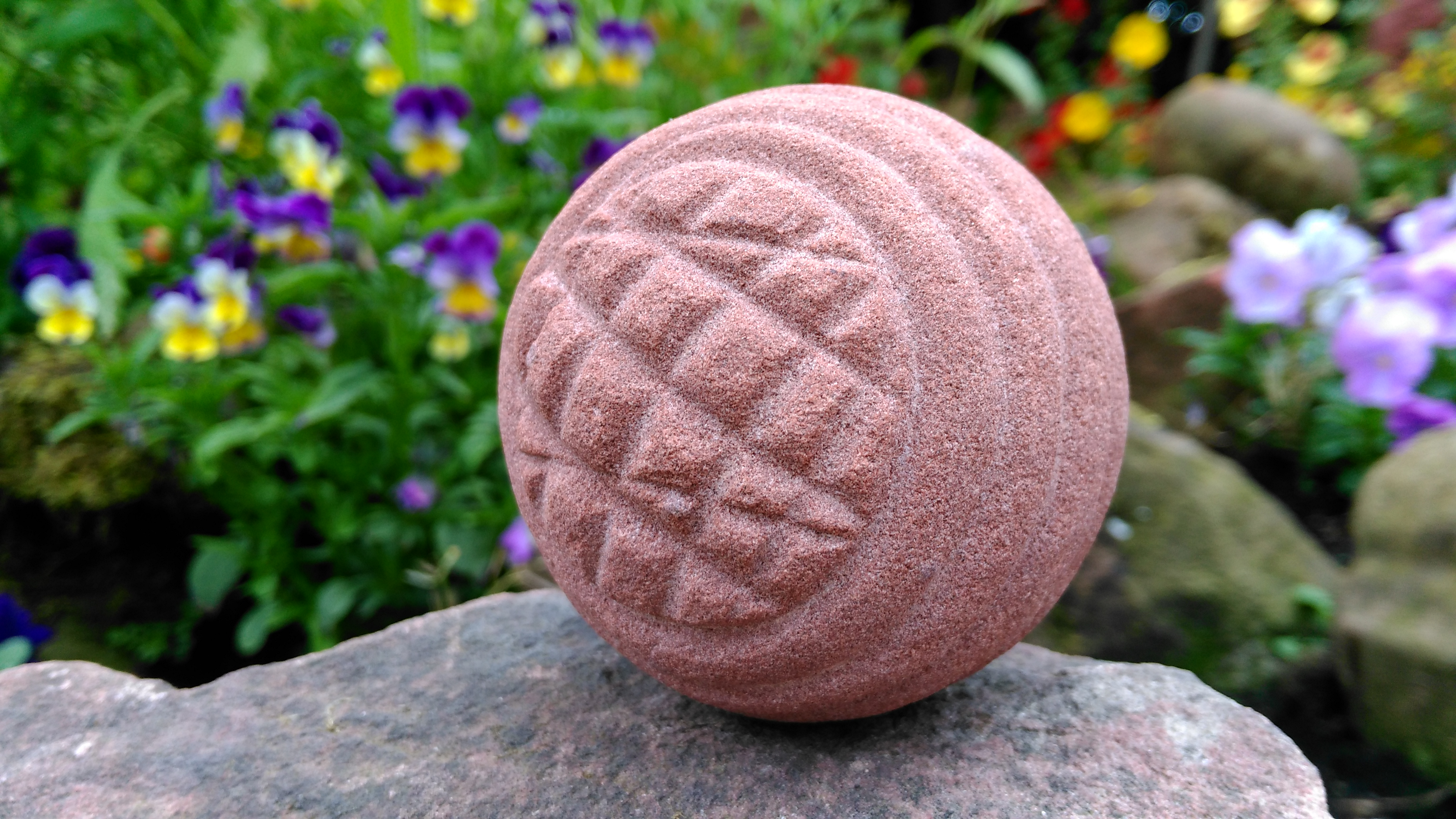 The form of this carved stone ball is based closely on a Late Neolithic ball found at Hillhead, St Ola, Orkney in the late 19th Century. The carved square patterns, chevrons and spiralling lines are also found on Orcadian Neolithic grooved ware pottery and decorated stonework. It is possible that the spiralling design and pleated chevron could provide a rare representation of an organic cord binding and wrapping around a carved stone ball that normally wouldn't survive. This ball has been pecked and carved to shape by Orcadian archaeologist Christopher Gee using the same local stone tools and techniques as used in the Late Neolithic. The ball is made from Orkney Red Sandstone which has been used for its colour and texture in architecture at the Ness of Brodgar. The central upright column in Stucture 10's central dresser was made from the same peck-dressed red sandstone. During the Middle Ages red sandstone was also used in St Magnus Cathedral and other high status Orcadian buildings.