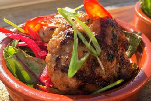 Grilled Thai pork putty with sliced chilli and spring onions on top