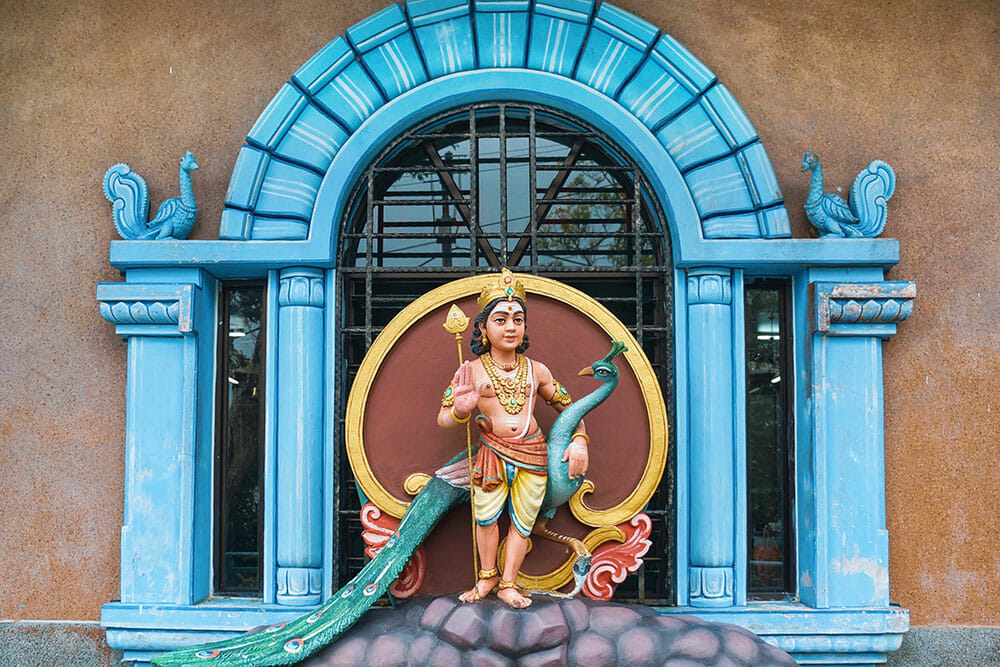 Hindu deity on a blue arched window from a Hindu temple