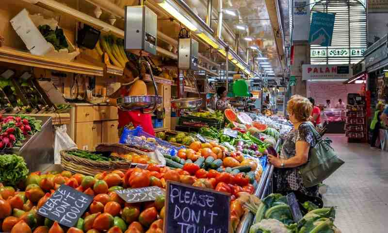 Woman shopping for fruit and vegetables at an indoor market stall in Valencia
