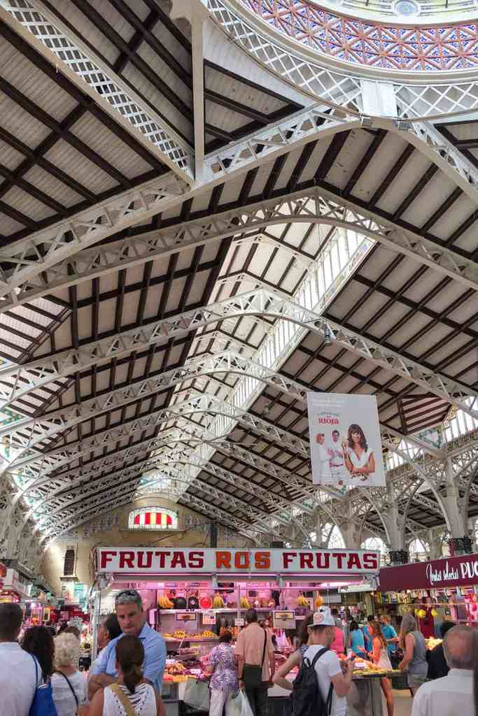 Modernist steel building with market stalls and people in Valencia