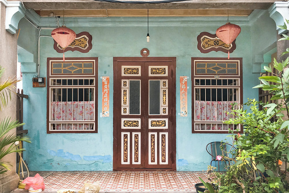 Blue Chinese shophouse with brown door and two brown windows and two pink lanterns