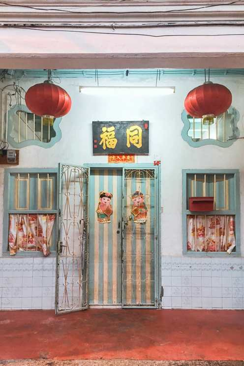 Chinese shophouse with blue and white striped door and two blue and white windows and two red lanterns