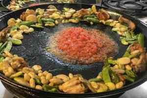 Grated tomatoes cooking with meat and vegetables on the edge of the paella pan