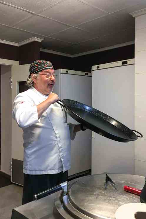 Chef showing a paella pan in the kitchen