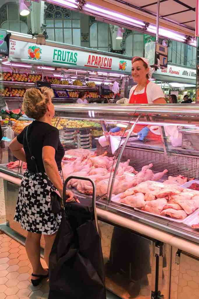Lady buying chickens from the market butcher in Valencia Central Market