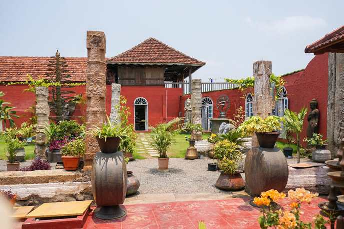 Courtyard with antiques and plant pots at Ginger House Cafe in Kochi