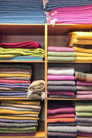 Colourful tweed blankets and scarves on a shelf