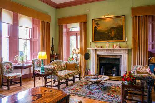 Room inside Glenveagh Castle with green walls and pink curtains