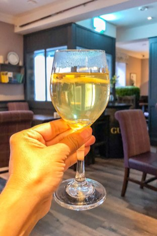 Holding a glass of honey coloured hot whiskey at Nesbitt Arms in Ardara