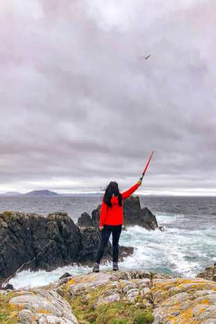 Staying on a rock facing the sea holding a light saber at Malin Head