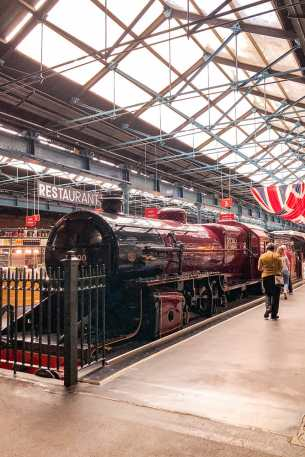 Red and black steam engine in a great hall
