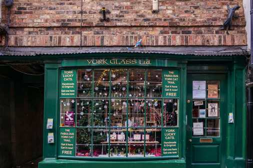 Green Victorian shop front of York Glass, with cat statue climbing up the wall