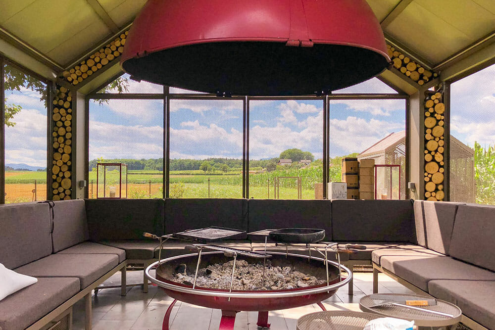 Enclosed area with barbecue pit in the middle surrounded by sofas